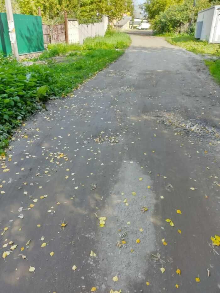 участок разбитой дороги без тротуаров